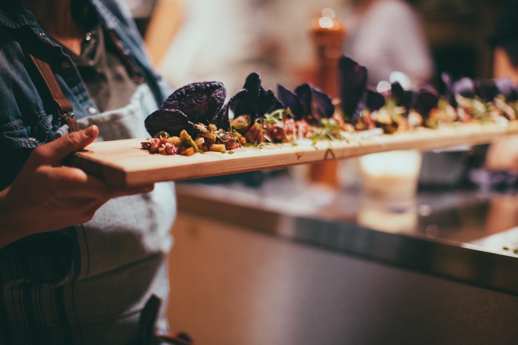Ein Holztablett mit angerichtetem Essen wird von einem Menschen ans Buffet getragen